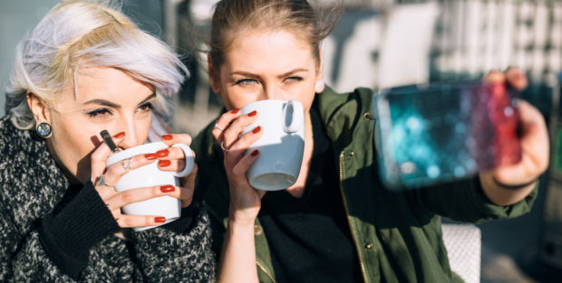 Picture shows two teenage girls drinking coffee and taking a selfie.