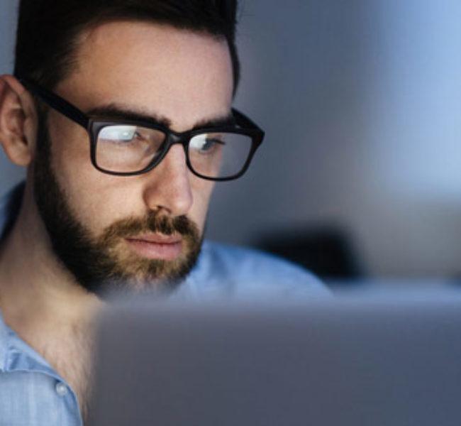 La photo montre un homme devant son ordinateur devant son ordinateur qui est en train d'analyser des données.