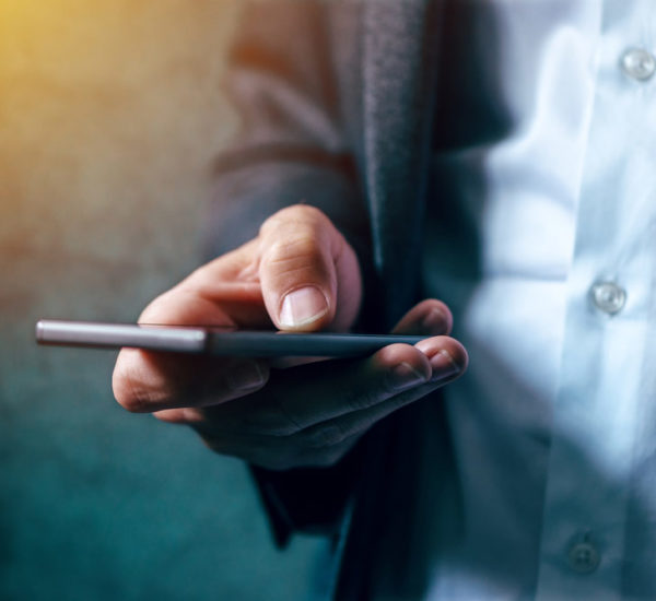 La photo montre un homme avec un smartphone en main.