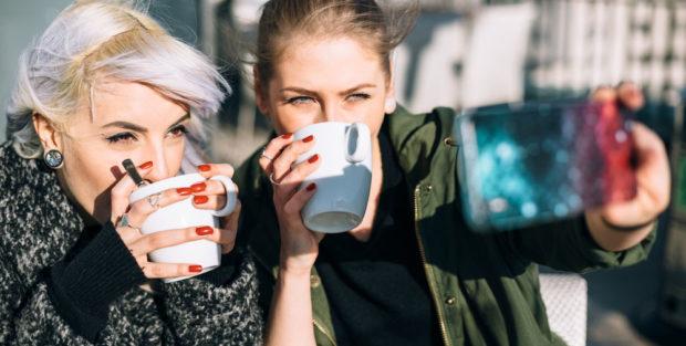 Bild zeigt zwei Mädchen, die Kaffee trinken und dabei ein Selfie machen.