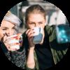 Zwei Mädchen trinken Kaffee und machen dabei ein Selfie.